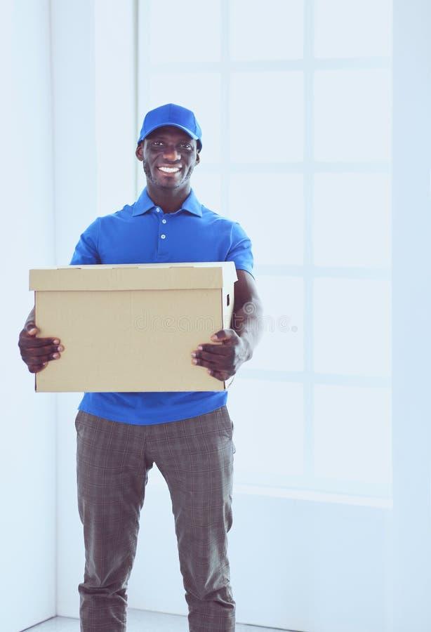 Ritratto di un deliverer felice bello con la scatola immagine stock libera da diritti