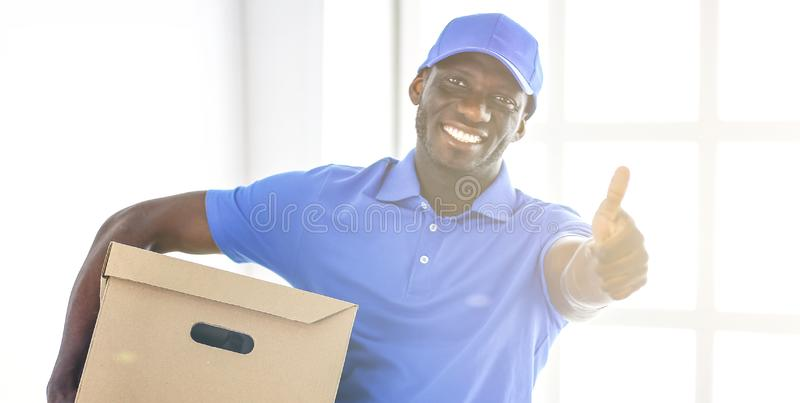 Ritratto di un deliverer felice bello con la scatola immagini stock libere da diritti