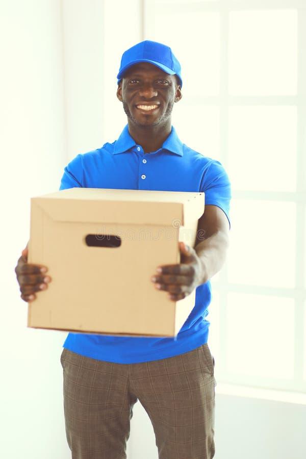 Ritratto di un deliverer felice bello con la scatola immagini stock