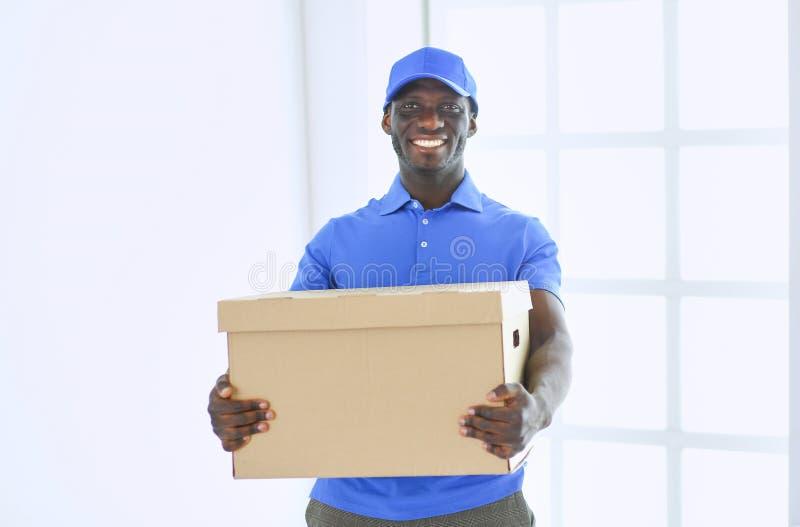 Ritratto di un deliverer felice bello con la scatola fotografie stock libere da diritti
