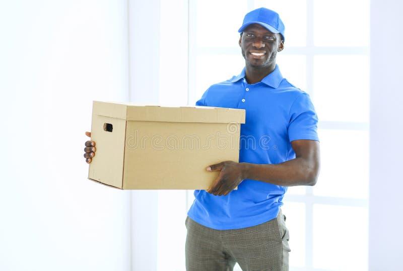 Ritratto di un deliverer felice bello con la scatola fotografia stock libera da diritti