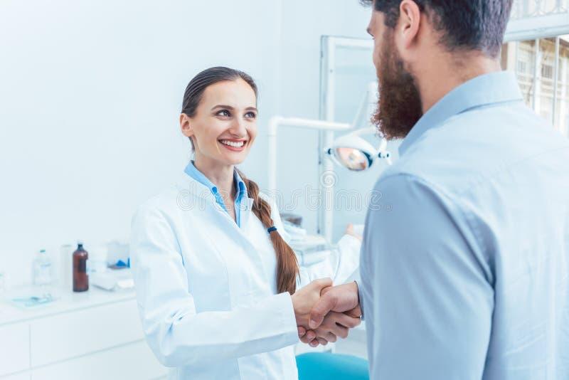 Ritratto di un dentista affidabile e allegro che stringe la mano di un paziente immagini stock