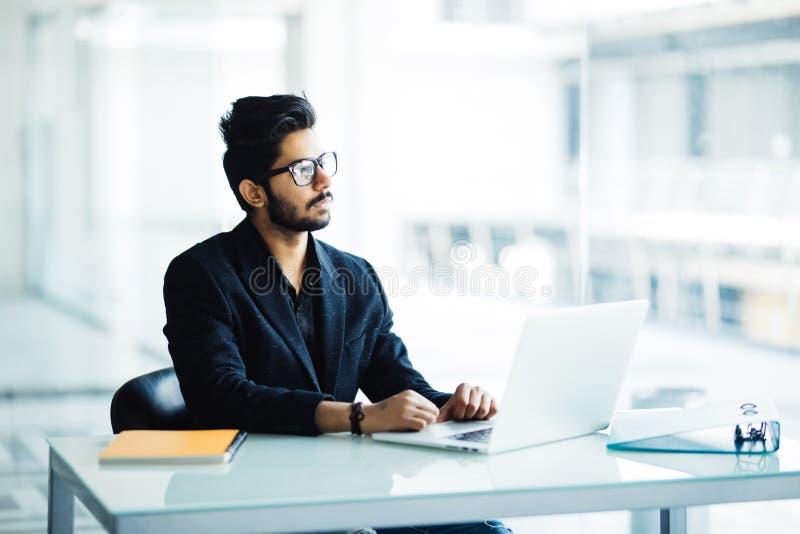 Ritratto di un'elaborazione multitask indiana occupata del tipo, prendendo le note, leggendo carta, Internet praticante il surfin fotografia stock