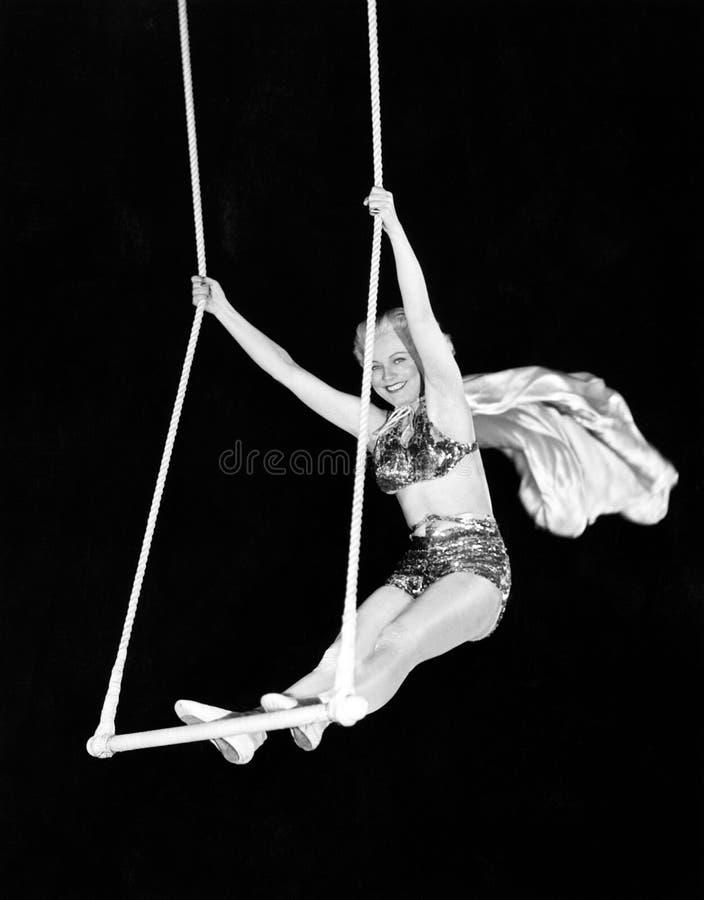 Ritratto di un esecutore di circo femminile che esegue su una barra del trapezio (tutte le persone rappresentate non sono vivente immagini stock libere da diritti
