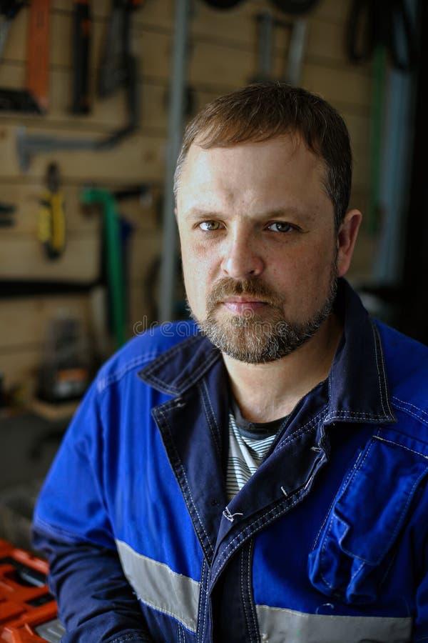 Ritratto di un fabbro in camici contro lo sfondo degli strumenti Maschio bianco sul lavoro che esamina la macchina fotografica fotografia stock