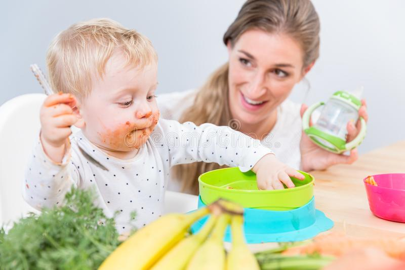 Ritratto di un fare da baby-sitter sveglio su seggiolone mentre mangiando alimento solido fotografia stock libera da diritti