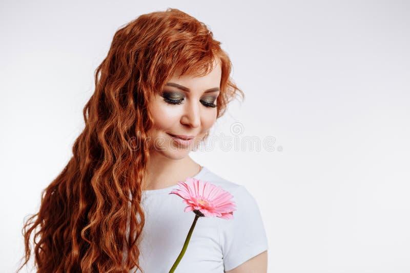 Ritratto di un fiore caucasico piacevole della tenuta della donna della testarossa su fondo bianco fotografie stock