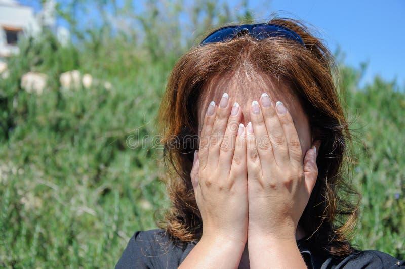 Ritratto di un fronte della copertura della giovane donna con le mani immagine stock