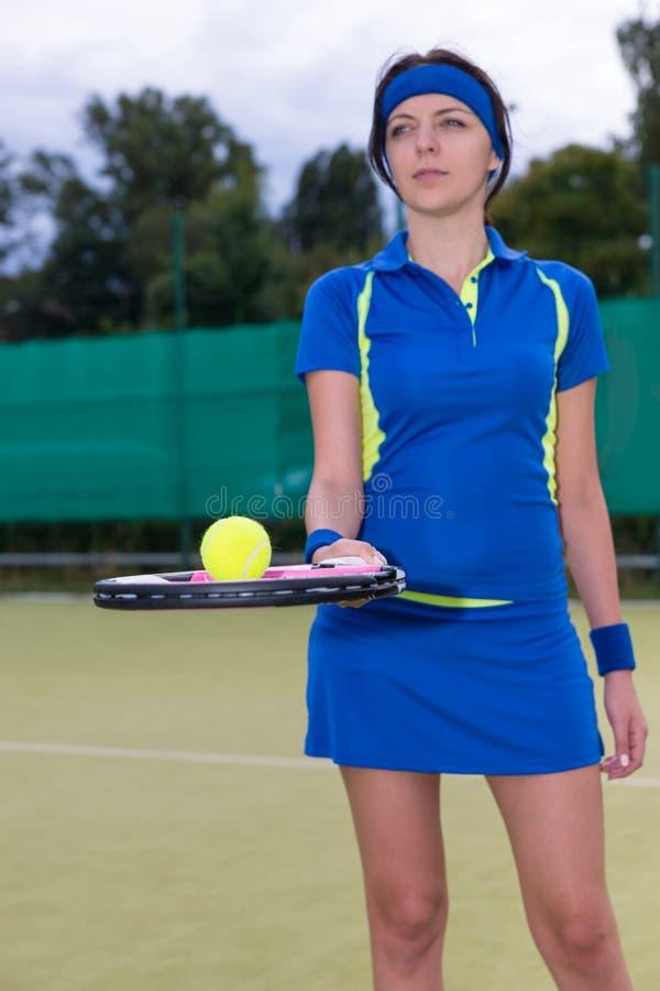 Ritratto di un giocatore femminile che tiene una pallina da tennis sulla sua racchetta immagini stock libere da diritti