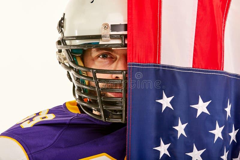 Ritratto di un giocatore di football americano su semichiuso dalla bandiera americana Primo piano, fondo bianco fotografia stock libera da diritti
