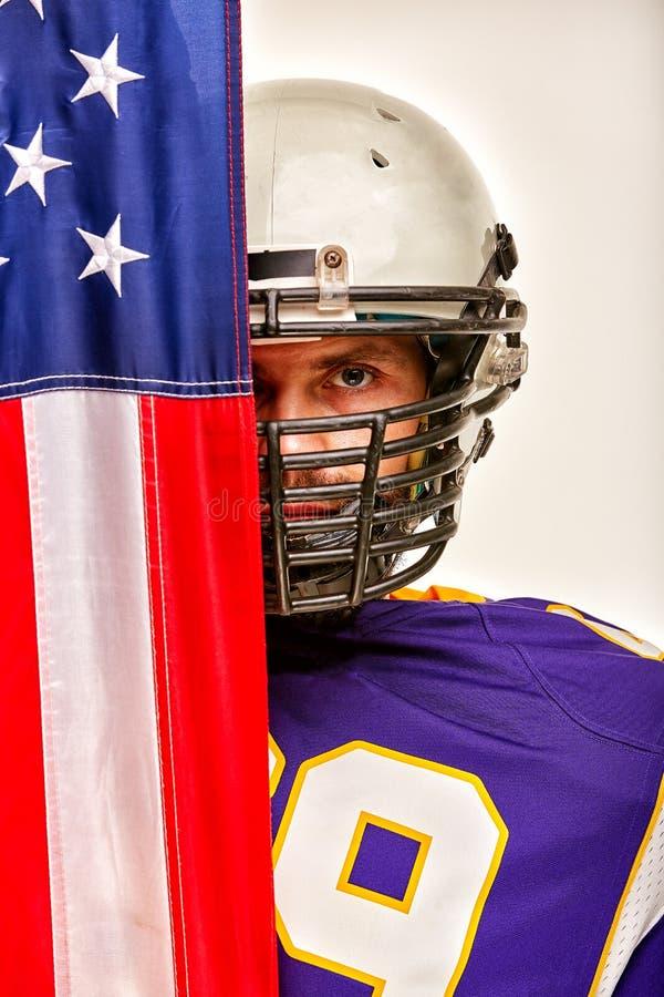 Ritratto di un giocatore di football americano su semichiuso dalla bandiera americana Primo piano, fondo bianco fotografie stock