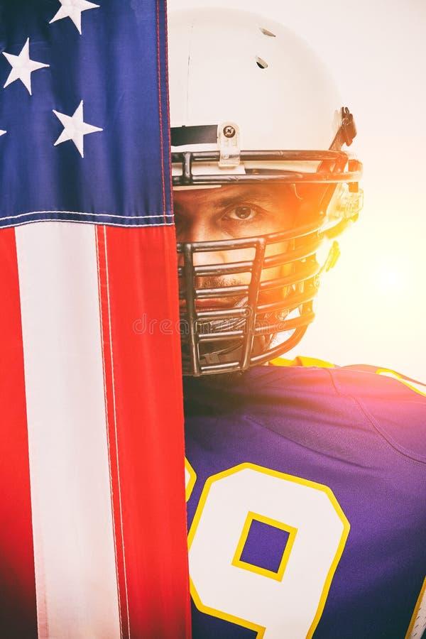 Ritratto di un giocatore di football americano su semichiuso dalla bandiera americana Primo piano, fondo bianco immagine stock