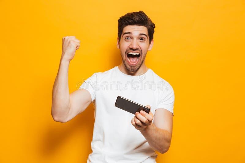 Ritratto di un giovane allegro che gioca sul telefono cellulare isolato sopra fondo giallo fotografie stock libere da diritti