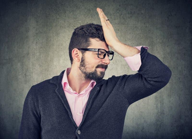 Ritratto di un giovane ansioso sollecitato, schiaffeggiante mano sulla testa che realizza errore immagini stock libere da diritti