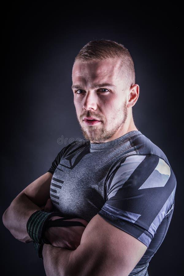 Ritratto di un giovane in attrezzatura di sport nello studio di forma fisica contro fondo scuro fotografia stock