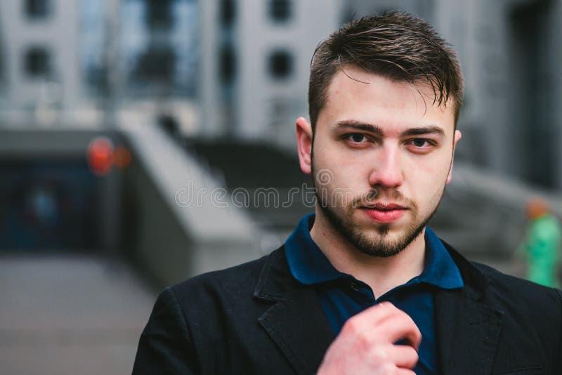 Ritratto di un giovane bello che esamina la macchina fotografica contro il contesto di architettura moderna Concetto di affari fotografia stock