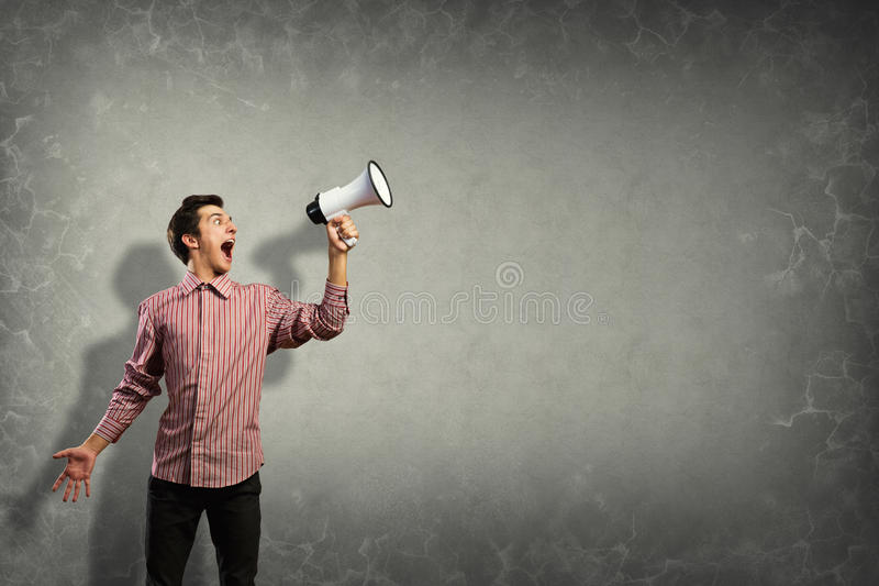 Ritratto di un giovane che grida facendo uso del megafono immagini stock