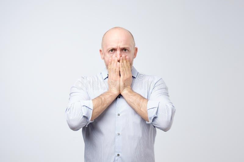 Ritratto di un giovane colpito che copre il suo bocca di mani fotografia stock