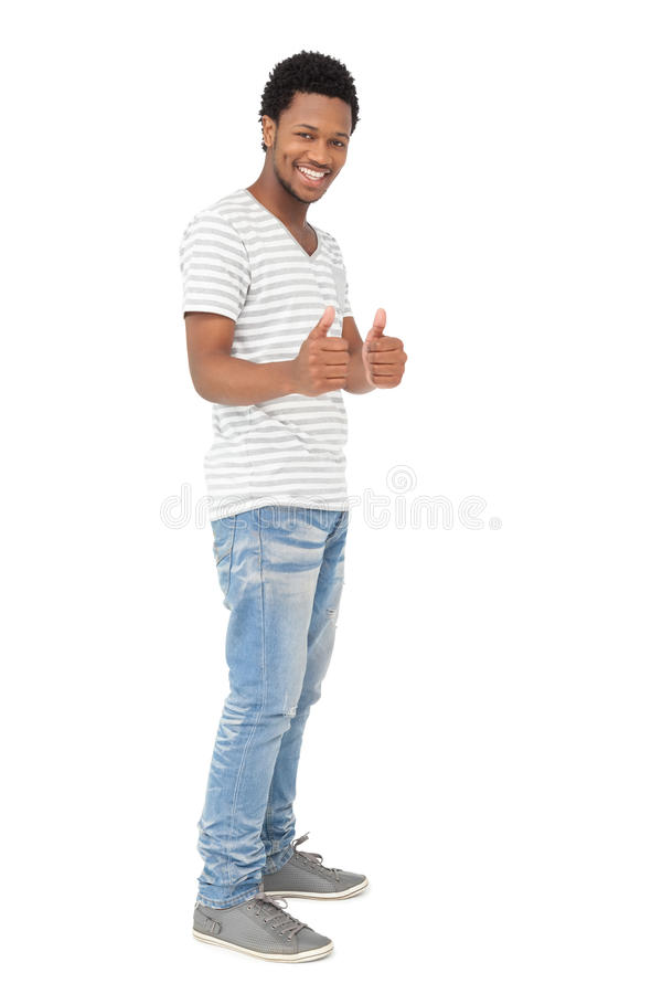 Ritratto di un giovane felice che gesturing i pollici su fotografie stock libere da diritti