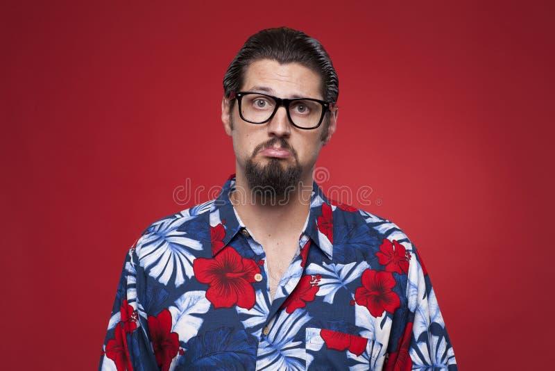 Ritratto di un giovane triste in camicia hawaiana contro backgr rosso fotografia stock