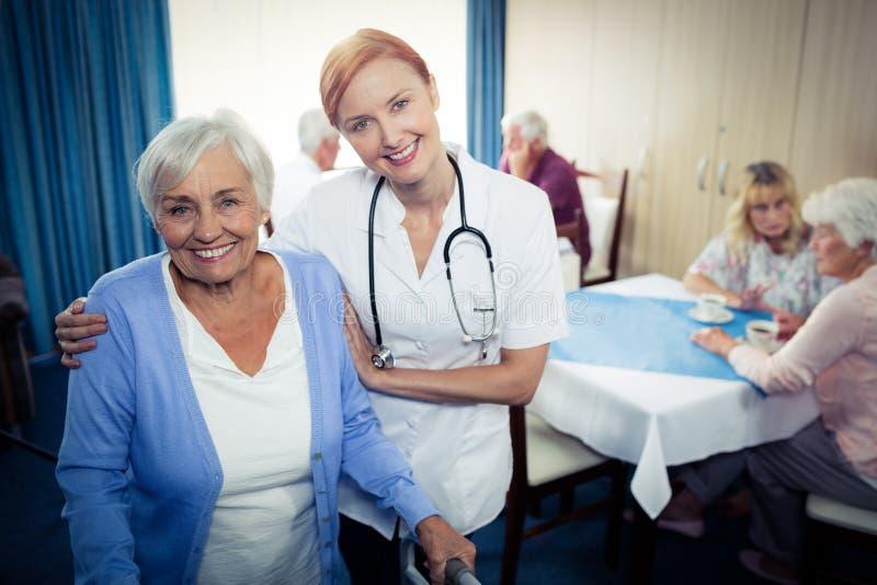 Ritratto di un infermiere che assiste un anziano che usando un camminatore fotografia stock libera da diritti