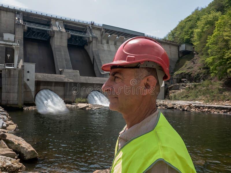 Ritratto di un lavoratore invecchiante in un casco contro il contesto delle turbine idroelettriche immagine stock libera da diritti