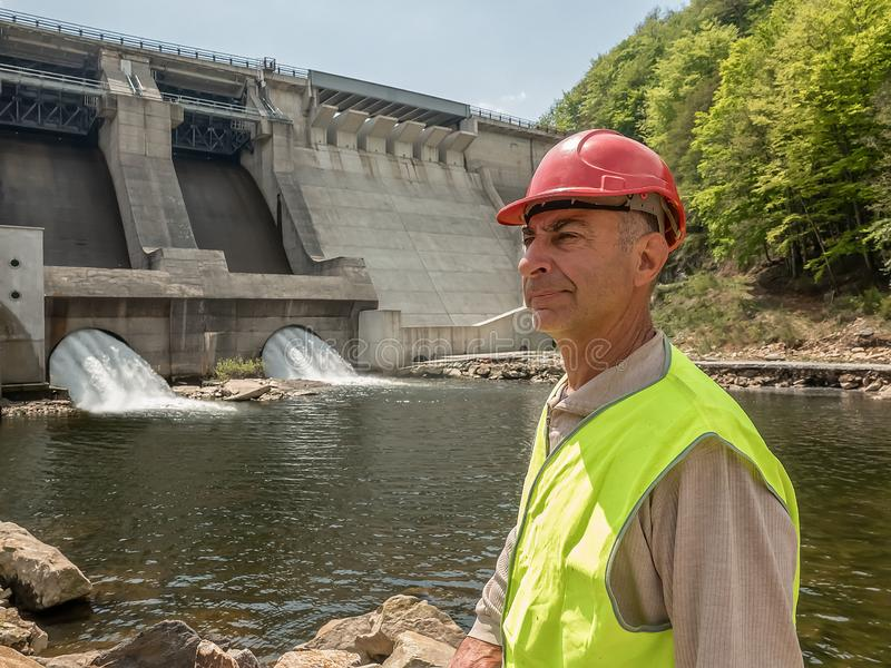 Ritratto di un lavoratore invecchiante in un casco contro il contesto delle turbine idroelettriche fotografia stock libera da diritti