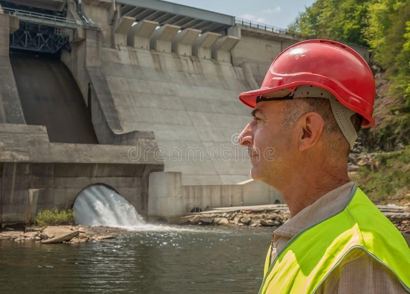 Ritratto di un lavoratore invecchiante in un casco contro il contesto delle turbine idroelettriche fotografia stock
