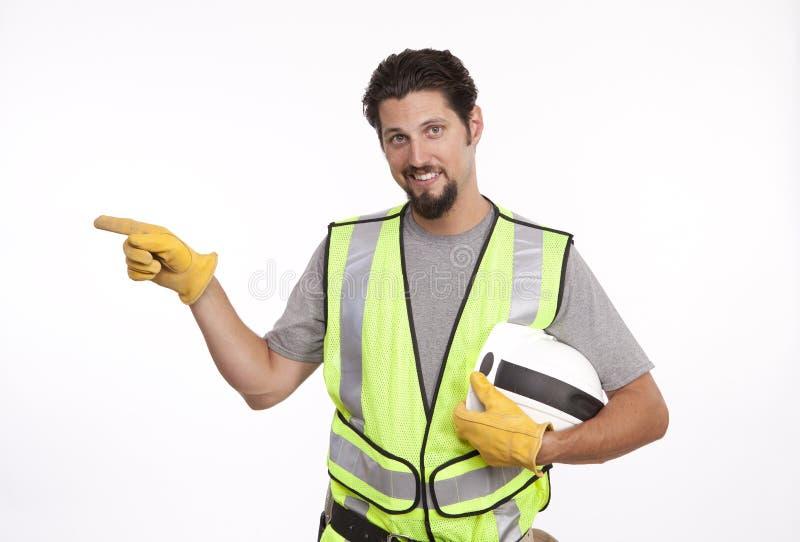 Ritratto di un lavoratore manuale sorridente che indica lateralmente fotografia stock libera da diritti