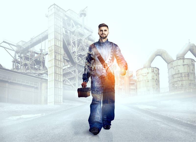 Ritratto di un lavoratore sul fondo della fabbrica immagini stock