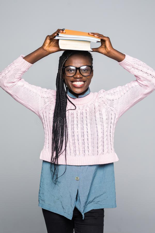 Ritratto di un libro africano della tenuta della ragazza sulla sua testa e di distogliere lo sguardo lo spazio della copia isolat immagine stock libera da diritti