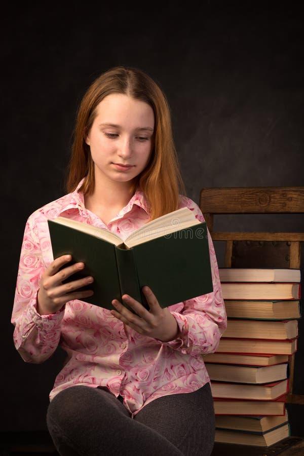 Ritratto di un libro di lettura della ragazza dell'adolescente vicino alla pila di libri immagine stock