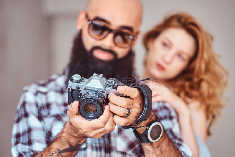 Ritratto di un maschio barbuto arabo che tengono una macchina fotografica e della sua bella amica della testarossa fotografia stock