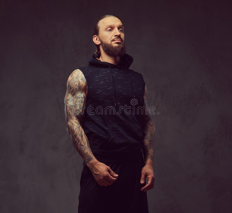 Ritratto di un maschio tattoed barbuto muscolare con un taglio di capelli alla moda che porta abiti sportivi neri, isolato su un  fotografie stock