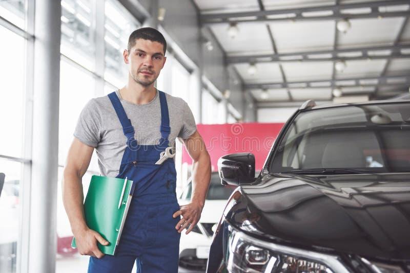 Ritratto di un meccanico sul lavoro nel suo garage - concetto di servizio, di riparazione, di manutenzione e della gente dell'aut fotografia stock libera da diritti