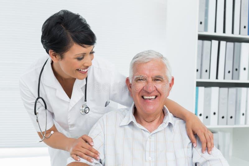 Ritratto di un medico femminile con il paziente senior felice immagini stock libere da diritti