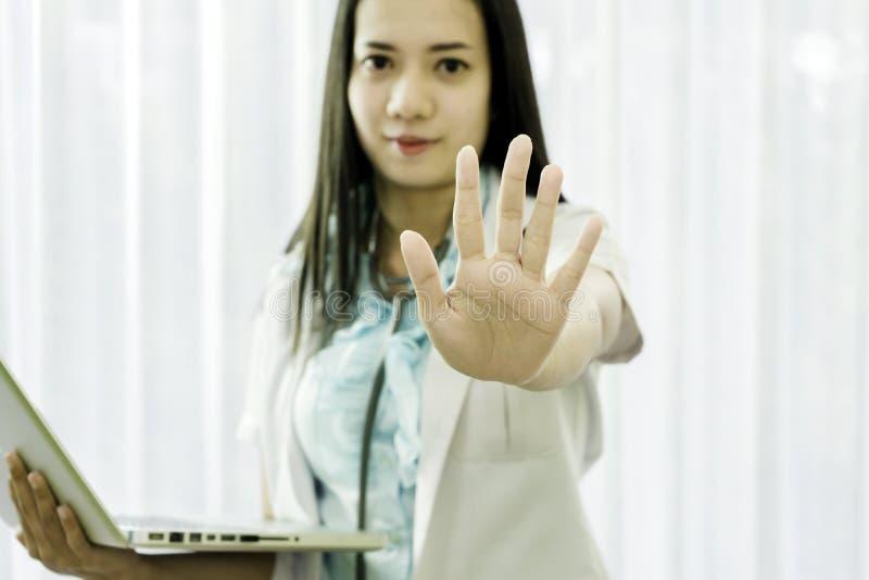 Ritratto di un medico femminile in un'uniforme bianca che sorride e che tiene un computer portatile in sua mano mentre sollevando fotografia stock