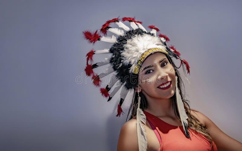 Ritratto di un modello latino con un copricapo messo le piume a in primo luogo immagini stock libere da diritti