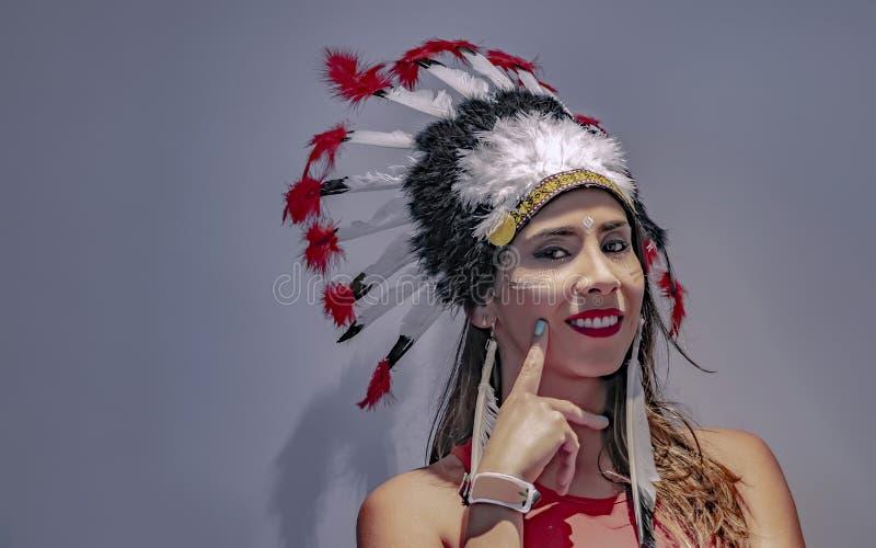 Ritratto di un modello latino con un copricapo messo le piume a in secondo luogo fotografia stock libera da diritti