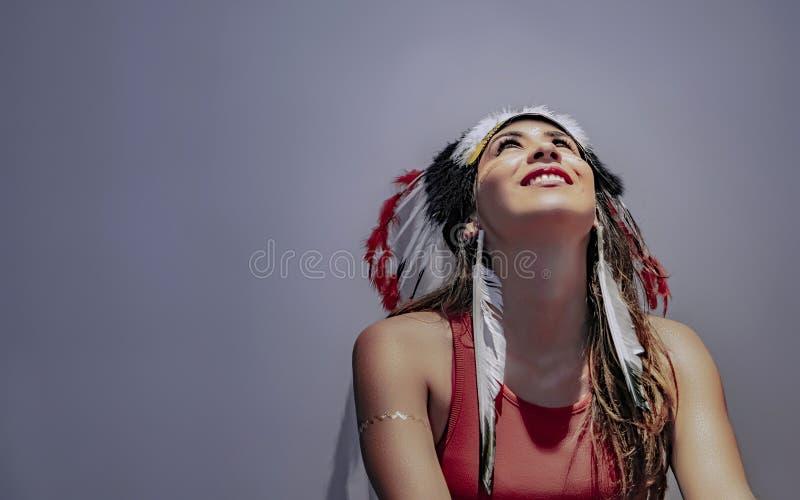 Ritratto di un modello latino con un quinto messo le piume a del copricapo fotografia stock