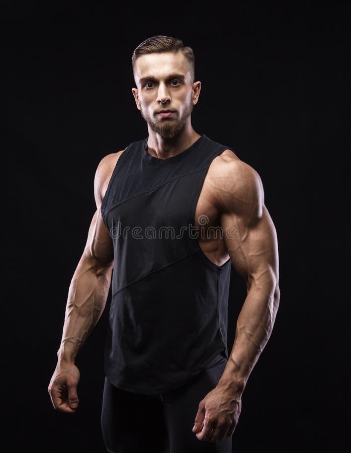 Ritratto di un modello maschio muscolare contro fondo nero fotografie stock