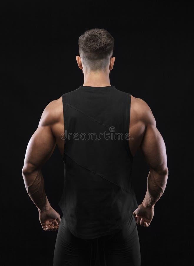 Ritratto di un modello maschio muscolare contro fondo nero fotografia stock