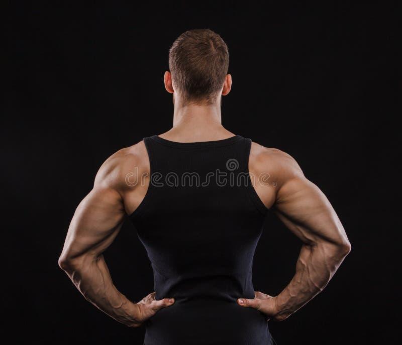 Ritratto di un modello maschio muscolare contro fondo nero fotografia stock libera da diritti