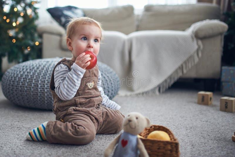 Ritratto di un neonato di 1 anno sveglio che si siede sul pavimento decorazioni di natale su un fondo immagine stock libera da diritti