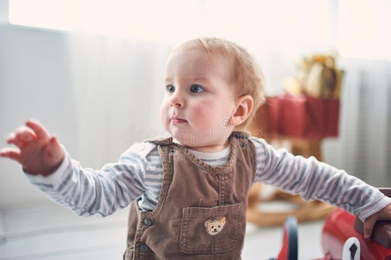 Ritratto di un neonato di 1 anno sveglio che si siede sul pavimento decorazioni di natale su un fondo immagini stock libere da diritti