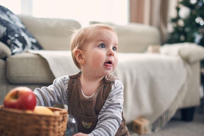Ritratto di un neonato di 1 anno sveglio che si siede sul pavimento decorazioni di natale su un fondo fotografia stock libera da diritti