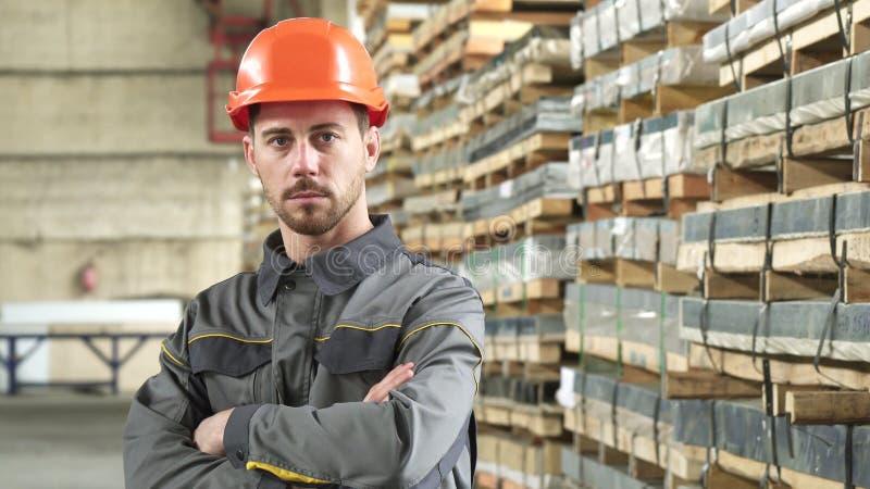 Ritratto di un operaio metallurgico serio bello che posa allo stoccaggio della fabbrica fotografia stock libera da diritti