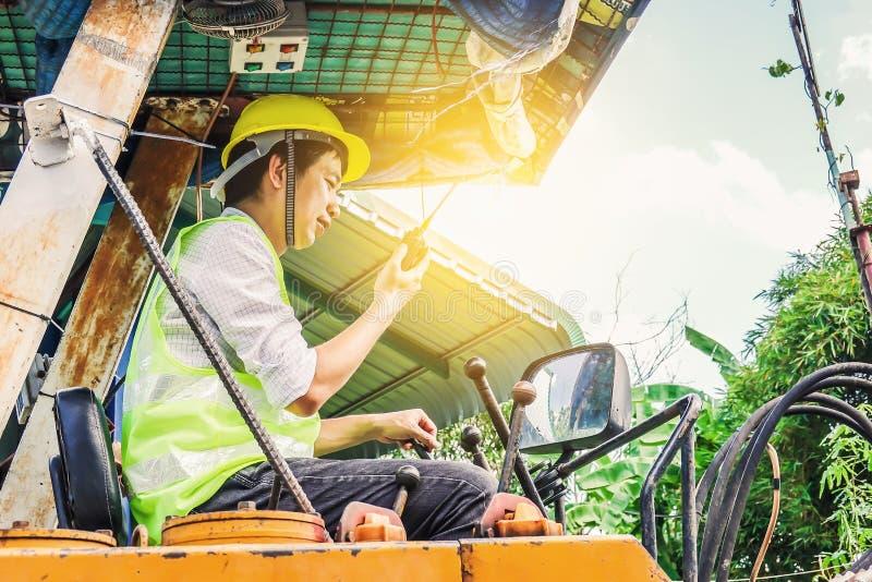 Ritratto di un operatore di seduta dello sviluppatore maschio che guida escavatore e che parla sul walkie-talkie fotografie stock