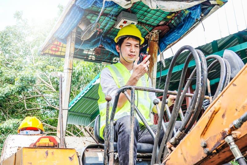Ritratto di un operatore di seduta dello sviluppatore maschio che guida escavatore e che parla sul walkie-talkie immagine stock libera da diritti
