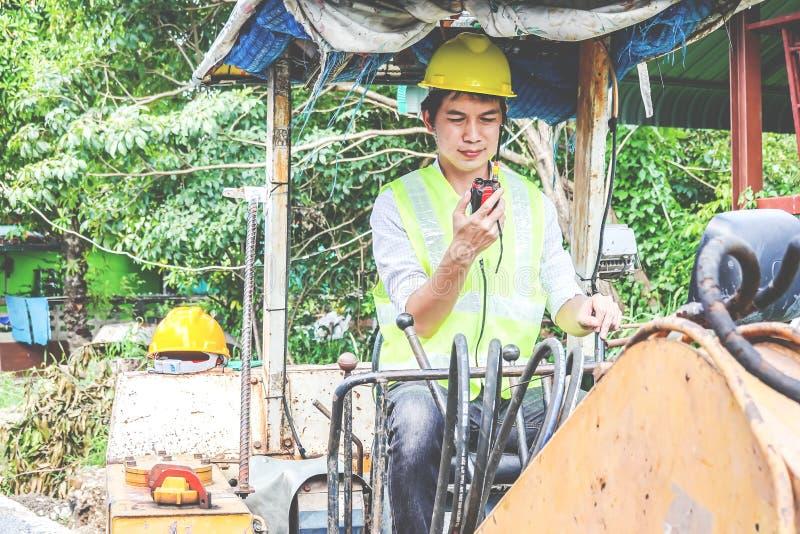 Ritratto di un operatore di seduta dello sviluppatore maschio che guida escavatore e che parla sul walkie-talkie immagine stock